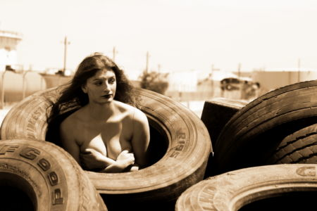 Implied Nude in a stack  of tires